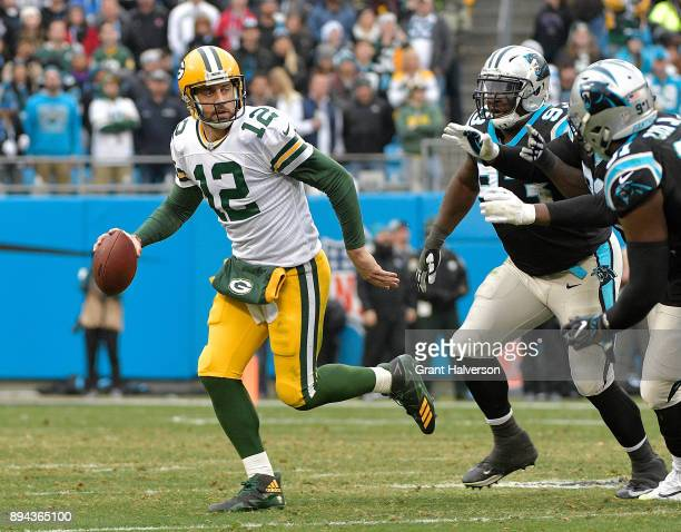 Aaron Rodgers of the Green Bay Packers rolls out under pressure from the Carolina Panthers defense during their game at Bank of America Stadium on...