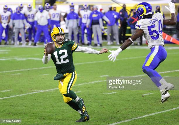 Aaron Rodgers of the Green Bay Packers runs against Leonard Floyd of the Los Angeles Rams for a 1-yard touchdown in the second quarter during the NFC...