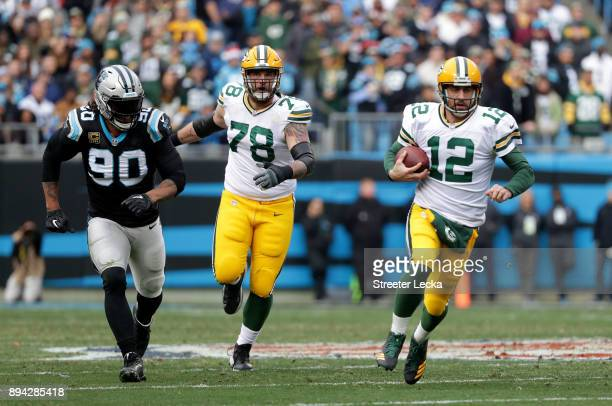 Aaron Rodgers of the Green Bay Packers runs the ball against the Carolina Panthers in the second quarter during their game at Bank of America Stadium...