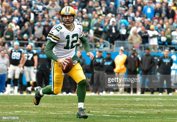 Aaron Rodgers of the Green Bay Packers runs with the ball against the Carolina Panthers in the second quarter during their game at Bank of America...
