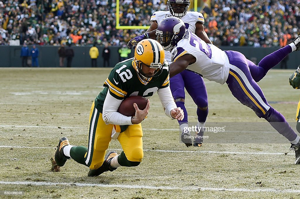 Aaron Rodgers #12 of the Green Bay Packers rushes for a touchdown during the second quarter of a game of a game against the Minnesota Vikings at Lambeau Field on December 24, 2016 in Green Bay, Wisconsin.