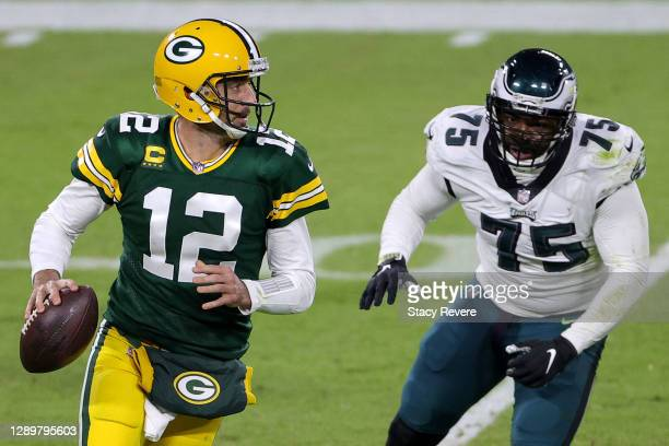 Aaron Rodgers of the Green Bay Packers scrambles to avoid a tackle from Vinny Curry of the Philadelphia Eagles during the fourth quarter of their...