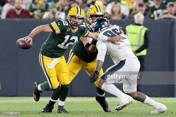 Aaron Rodgers of the Green Bay Packers scrambles while being pressured by Derek Barnett of the Philadelphia Eagles in the third quarter at Lambeau...