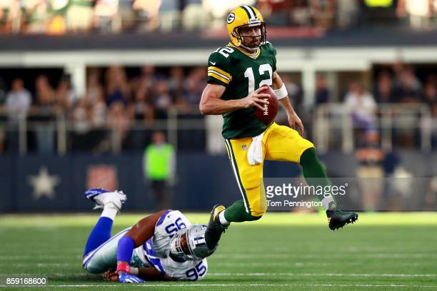 Aaron Rodgers of the Green Bay Packers scrambles with the ball against David Irving of the Dallas Cowboys in the fourth quarter at ATT Stadium on...