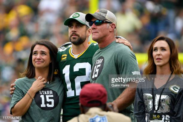 Aaron Rodgers of the Green Bay Packers shares a moment with former quarterback Brett Favre during a ceremony for the late Bart Starr at halftime of...