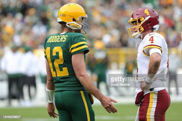 Aaron Rodgers of the Green Bay Packers speaks with Taylor Heinicke of the Washington Football Team during a game at Lambeau Field on October 24, 2021...