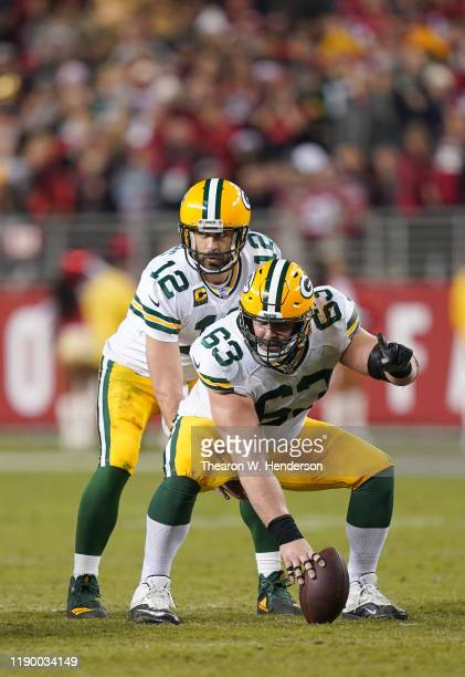 Aaron Rodgers of the Green Bay Packers stands under center Corey Linsley against the San Francisco 49ers during the second half of an NFL football...