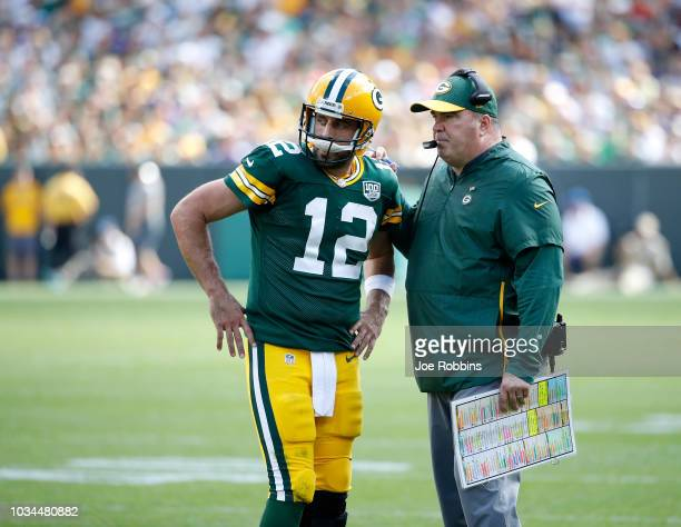 Aaron Rodgers of the Green Bay Packers talks with head coach Mike McCarthy during the fourth quarter of a game against the Minnesota Vikings at...