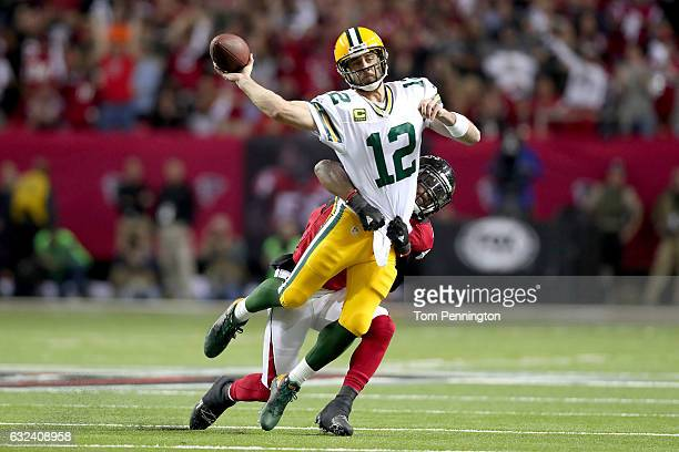 Aaron Rodgers of the Green Bay Packers throws as he is hit by Deion Jones of the Atlanta Falcons in the first quarter in the NFC Championship Game at...