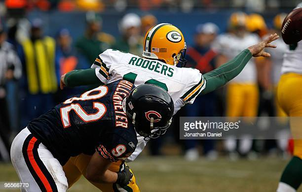 Aaron Rodgers of the Green Bay Packers tosses the ball as he is brought down by Hunter Hillenmeyer of the Chicago Bears at Soldier Field on December...