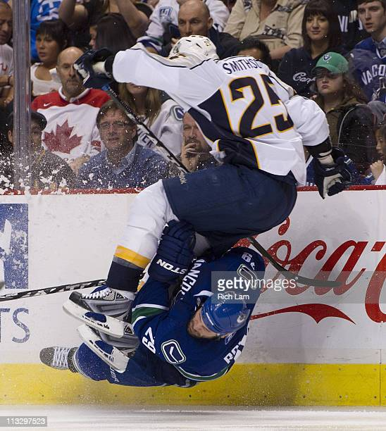 Aaron Rome of the Vancouver Canucks collides with Jerred Smithson of the Nashville Predators while falling during the second overtime period in Game...