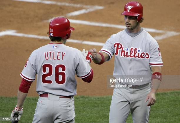 Aaron Rowand of the Philadelphia Phillies is congratulated by teammate Chase Utley after scoring the Phillies first run on a sacrifice fly in the 1st...