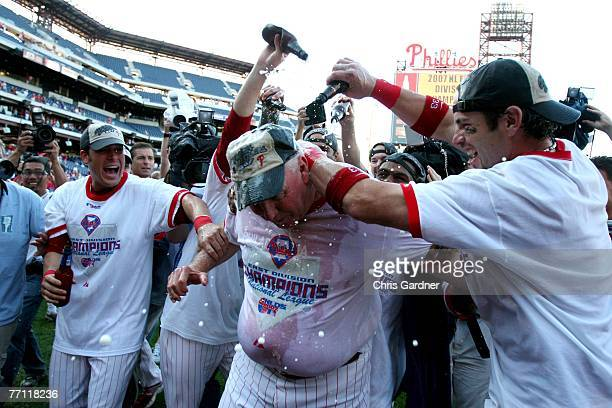 Aaron Rowand of the Philadelphia Phillies pours beer over the head of Phillies manager Charlie Manuel center as other teammates celebrate at Citizens...