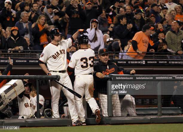 Aaron Rowand of the San Francisco Giants is congratulated by Aubrey Huff after he scored on a wild pitch by Armando Galarraga of the Arizona...