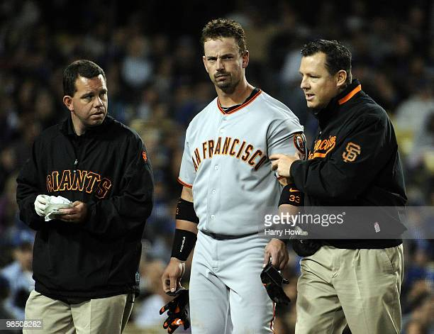 Aaron Rowand of the San Francisco Giants is helped off the field by trainers after being hit in the head by a pitch from Vicente Padilla of the Los...