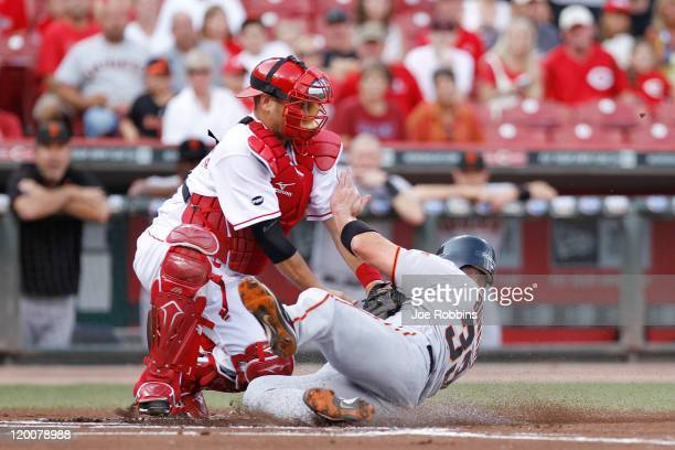 Aaron Rowand of the San Francisco Giants slides at home plate to score a run in the first inning ahead of the tag of Ramon Hernandez of the...