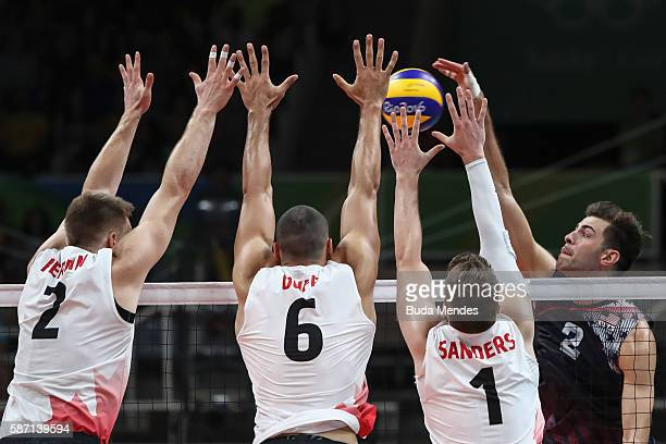 Aaron Russell of the United States jumps to spike the ball against Jonh Gordon Perrin Justin Duff and Tyler Sandres during the Men's Preliminary Pool...
