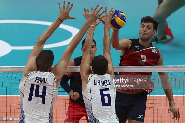 Aaron Russell of the United States spikes the ball against Matteo Piano and Simone Giannelli of Italy during the men's qualifying volleyball match...