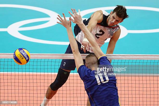 Aaron Russell of United States spikes against Kevin le Roux of France during a Men's Preliminary Pool B match on Day 8 of the Rio 2016 Olympic Games...