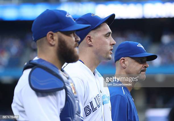 Aaron Sanchez of the Toronto Blue Jays and Russell Martin and pitching coach Pete Walker make their way from the bullpen to the dugout before the...