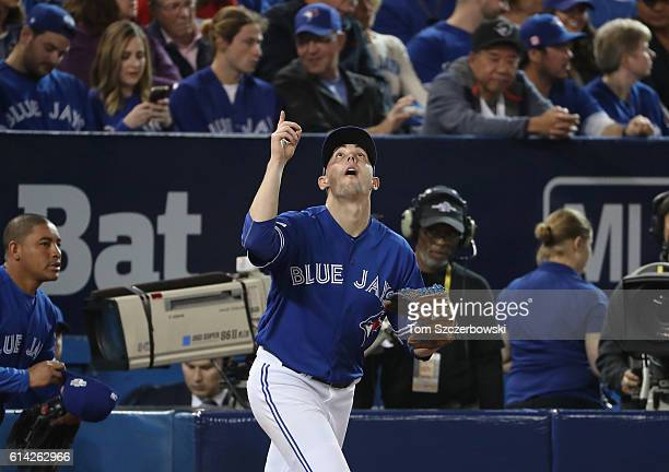 Aaron Sanchez of the Toronto Blue Jays points at the sky as he comes out to pitch the third inning during MLB game action against the Texas Rangers...