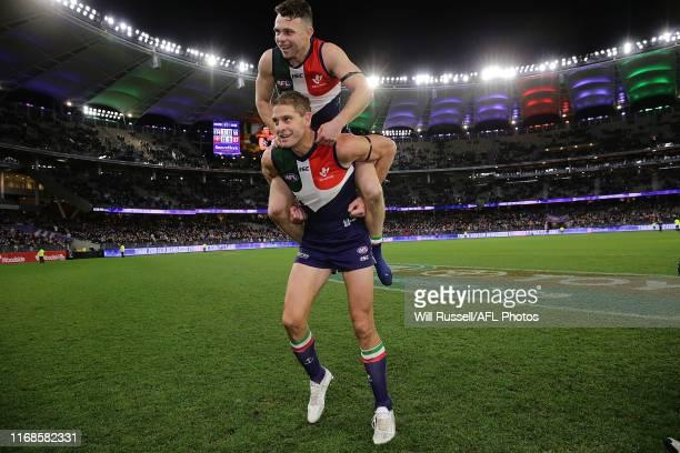 Aaron Sandilands carries Hayden Ballantyne of the Dockers on his shoulders after the round 22 AFL match between the Fremantle Dockers and the...