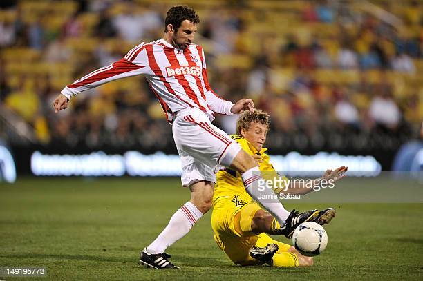 Aaron Schoenfeld of the Columbus Crew slides in to take the ball away from Danny Higginbotham of Stoke City FC in the second half on July 24 2012 at...