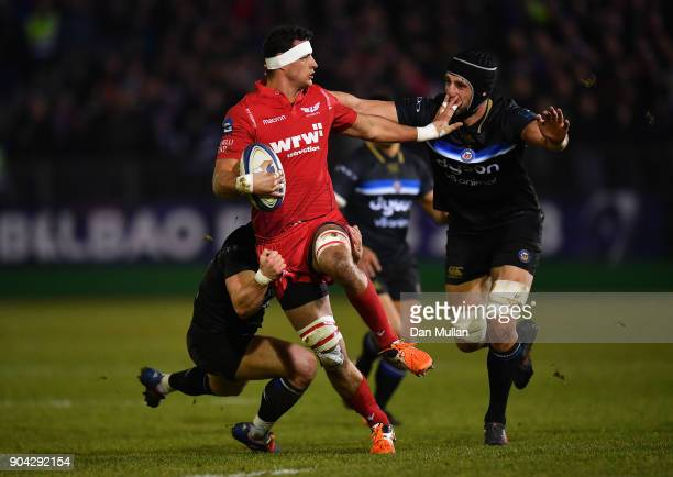 Aaron Shingler of Scarlets is tackled by Chris Cook and Luke Charteris of Bath during the European Rugby Champions Cup match between Bath Rugby and...