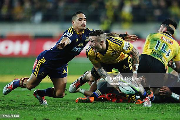 Aaron Smith of the Highlanders defends as TJ Perenara of the Hurricanes looks to pass the ball out during the Super Rugby Final match between the...