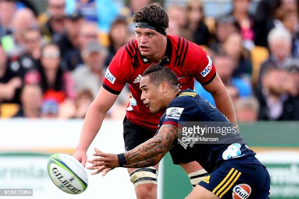 Aaron Smith of the Highlanders passes the ball as Scott Barrett of the Crusaders looks on during the Super Rugby trial match between the Highlanders...