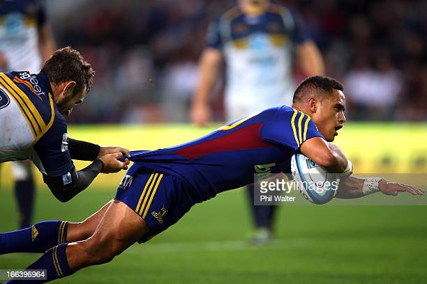 Aaron Smith of the Highlanders scores a try in the hold of Nic White of the Brumbies during the round nine Super Rugby match between the Highlanders...