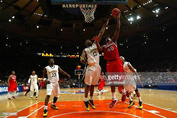 Aaron Spears of the St Johns Red Storm goes to the hoop against Dwight Burke of the Marquette Golden Eagles during the first round of the Big East...