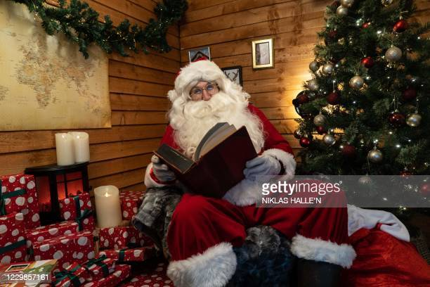 Aaron Spenedelow dressed up as Santa Claus speaks to the camera during a Zoom call with a family, as Santa's Grotto Live gets underway in Wembley,...