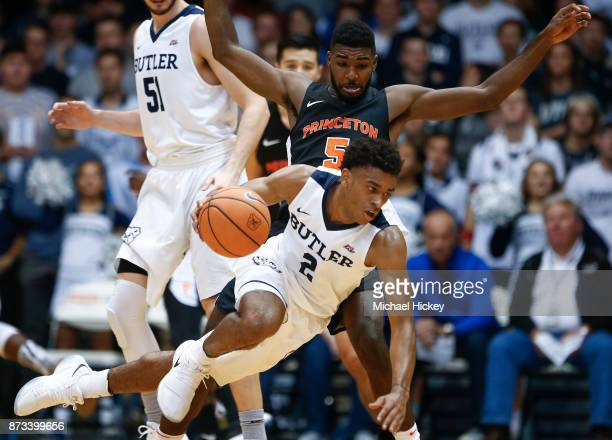 Aaron Thompson of the Butler Bulldogs trips while dribbling as Amir Bell of the Princeton Tigers defends at Hinkle Fieldhouse on November 12 2017 in...