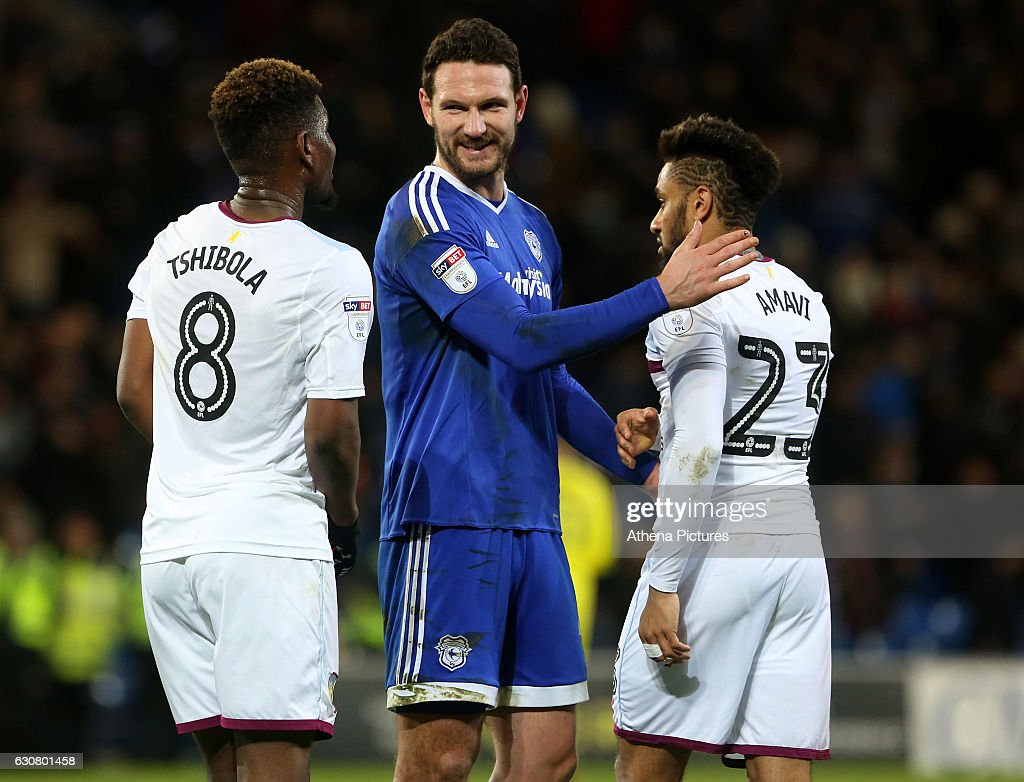 Aaron Tshibola of Aston Villa laughs with Captian Sean Morrison of Cardiff City as he pats Jordan Amavi of Aston Villa on the back after the final whistle of the Sky Bet Championship match between Cardiff City and Aston Villa at The Cardiff City Stadium on January 02, 2017 in Cardiff, Wales.