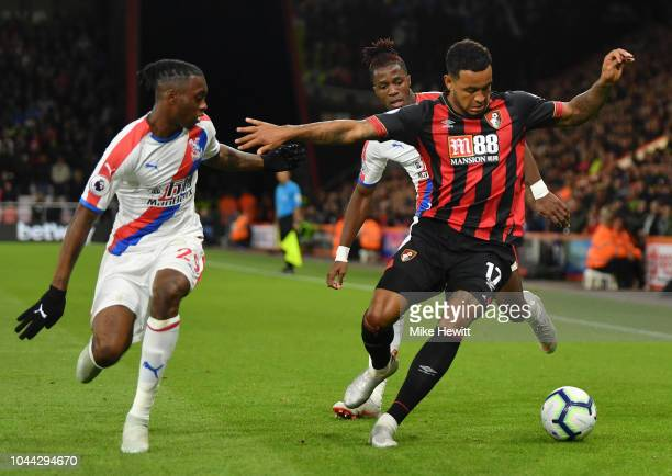 Aaron WanBissaka of Crystal Palace looks on as Joshua King of AFC Bournemouth controls the ball as Wilfried Zaha of Crystal Palace looks on during...