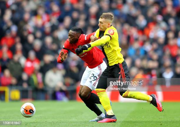 Aaron WanBissaka of Manchester United and Gerard Deulofeu of Watford battle for possession during the Premier League match between Manchester United...
