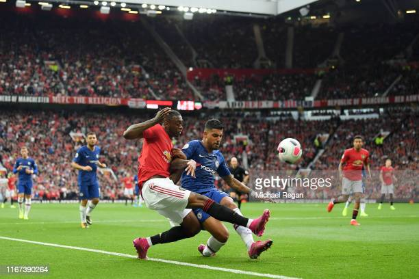 Aaron WanBissaka of Manchester United crosses the ball under pressure from Emerson Palmieri of Chelsea during the Premier League match between...