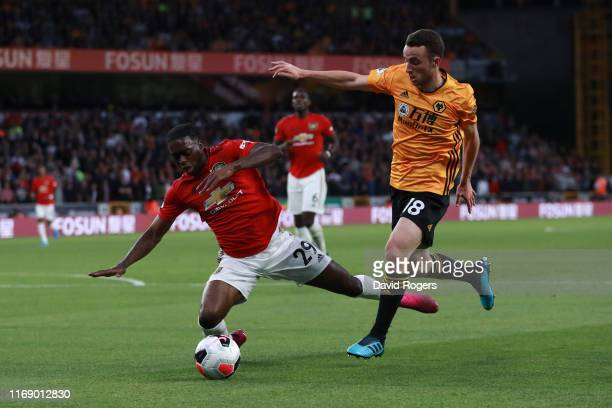 Aaron WanBissaka of Manchester United is brought down by Diogo Jota of Wolverhampton Wanderers during the Premier League match between Wolverhampton...