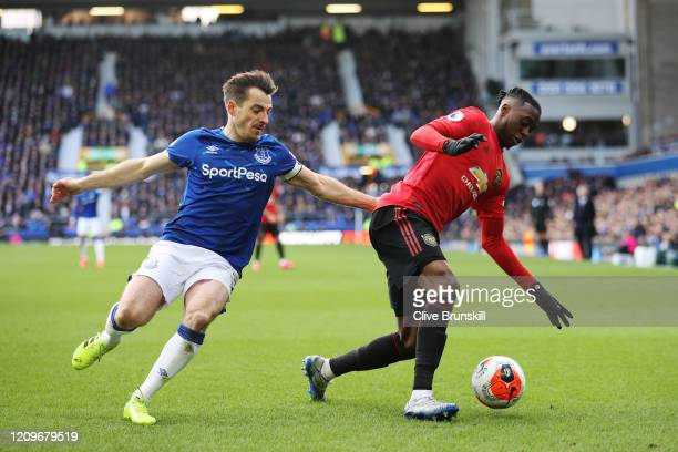 Aaron WanBissaka of Manchester United is challenged by Leighton Baines of Everton during the Premier League match between Everton FC and Manchester...