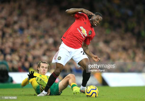 Aaron WanBissaka of Manchester United is tackled by Todd Cantwell of Norwich City during the Premier League match between Norwich City and Manchester...