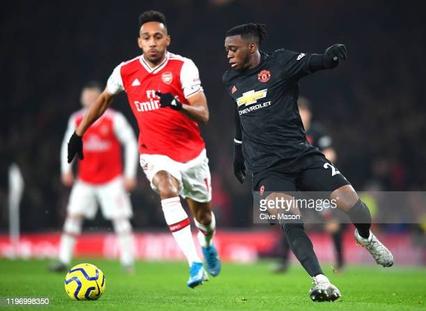 Aaron Wan-Bissaka of Manchester United runs away from Pierre-Emerick Aubameyang of Arsenal during the Premier League match between Arsenal FC and...