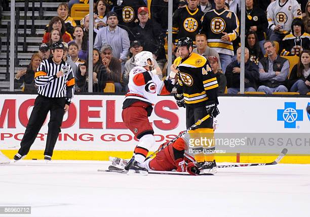 Aaron Ward of the Boston Bruins gets punched by Scott Walker of the Carolina Hurricanes during Game Five of the Eastern Conference Semifinal round of...