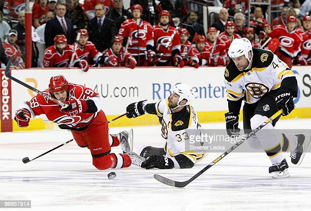 Aaron Ward of the Boston Bruins goes after a puck as his teammate Zdeno Chara collides with Chad LaRose of the Carolina Hurricanes during Game Four...