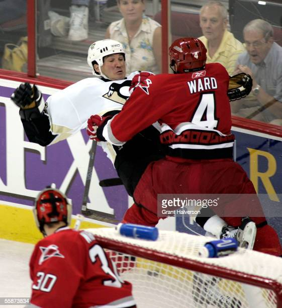 Aaron Ward of the Carolina Hurricanes checks Mario Lemieux of the Pittsburgh Penguins during the second period of an NHL game on October 7, 2005 at...
