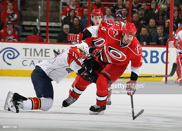 Aaron Ward of the Carolina Hurricanes pushes through a defensive attempt by David Booth of the Florida Panthers during the second period of their NHL...