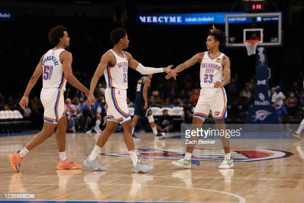 Aaron Wiggins and Tre Mann of the Oklahoma City Thunder hi-five during a preseason game against the Denver Nuggets on October 13, 2021 at Paycom...