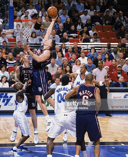 Aaron Williams of the New Jersey Nets rebounds over Darrell Armstrong of the Orlando Magic during the NBA game at TD Waterhouse Centre on February 11...