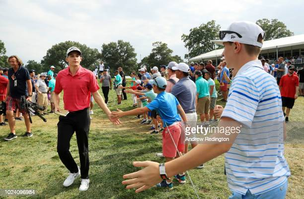 Aaron Wise of the United States greets fans between the 15th and 16th holes during the final round of The Northern Trust on August 26, 2018 at the...