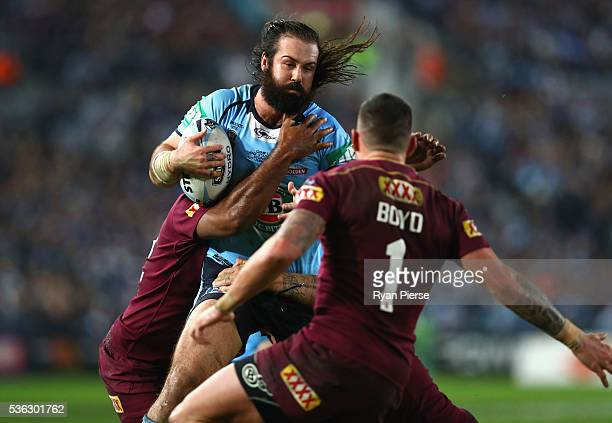 Aaron Woods of the Blues is tacked during game one of the State Of Origin series between the New South Wales Blues and the Queensland Maroons at ANZ...